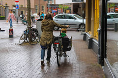 A woman carries a child by bicycle in the  historic center Stock Photography