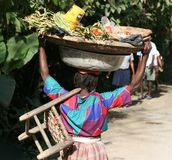 Woman carries goods on head and body in Haiti. Royalty Free Stock Photography