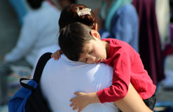 Woman carries his sleep son. A young mother carries his son on his shoulder because the kid fall sleep in a massive event in mexico Stock Photography