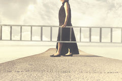 Woman carries a long ladder to climb into the sky Stock Images