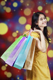 Woman carries shopping bags with bokeh background Stock Images