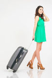Woman carries your luggage at the airport terminal. Suitcase. Traveler girl dressed in summer green dress. Tourism. Tourist bag. Travel to south of Thailand Royalty Free Stock Photo