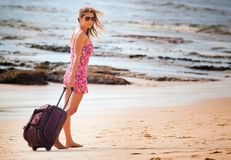 Woman carries your luggage at sandy beach Stock Photo
