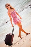 Woman carries your luggage at sandy beach Stock Photos