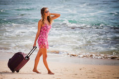 Woman carries your luggage at sandy beach Stock Image