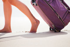 Woman carries your luggage at sandy beach Stock Images