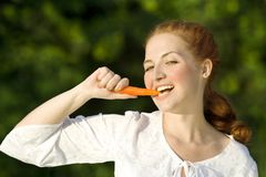 Woman with carrot. Smiling woman eat red carrot Stock Photos