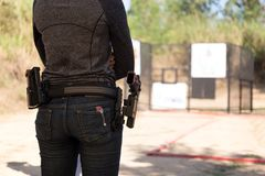 Woman carry gun in his waistband. At shooting range stock image