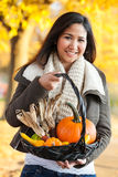 Woman carrying autumn harvest basket Stock Image