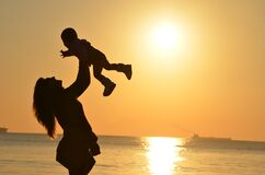 Woman Carrying Baby at Beach during Sunset royalty free stock photos