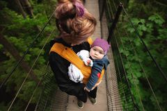 Woman Carrying Baby on Bridge stock images