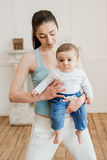 Woman carrying baby child on arms at home Royalty Free Stock Images