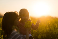 Woman carrying baby girl in her arms on rapeseed field Royalty Free Stock Photo