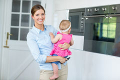 Woman carrying baby girl in kitchen Stock Images
