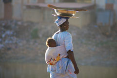 Woman carrying a baby in Mopti. MALI, MOPTI, DECEMBER 28: Unidentified Woman carrying a baby in her back in the streets of Mopti. 2010 Stock Photo