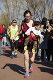 Woman carrying baby and running in Beijing Color Run Event. Beijing Color Run is a yearly public sport event in winter in Beijing Olympic Park. People without Royalty Free Stock Image