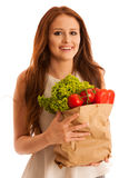 Woman carrying a bag full of various vegetables isolated over wh Stock Photo