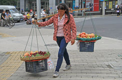 Woman is carrying balancing arm with baskets of Stock Photography