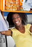 Woman Carrying Basket Of Clothes In Laundromat Royalty Free Stock Photo
