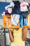 Woman Carrying Basket Of Dirty Clothes In Front Of Royalty Free Stock Photos
