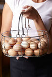 Woman carrying basket of eggs Stock Photography