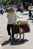 Woman carrying a basket of fruit in hanoi. Woman carrying a basket of fruit on a bicycle in hanoi stock photography