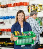 Woman Carrying Basket Full Of Tools In Store Stock Photography
