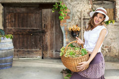 Woman carrying basket of grapes Royalty Free Stock Image