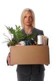 Woman Carrying Belongings in Box. Sad businesswoman carrying belongings in box after loosing job Stock Image