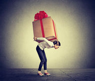 Woman carrying  big present on her back Royalty Free Stock Photo