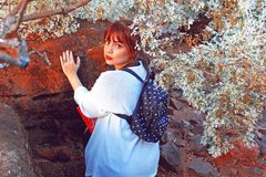 Woman Carrying Blue Backpack Leaning on Rock stock photography