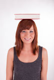 A woman is carrying books on her head Royalty Free Stock Images