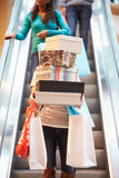 Woman Carrying Boxes And Bags In Shopping Mall. Coming Down Escalator Royalty Free Stock Photo