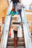 Woman Carrying Boxes And Bags In Shopping Mall. On Escalator With People Behind Royalty Free Stock Image