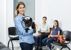 Woman Carrying Bulldog With Cone In Clinic Stock Photo