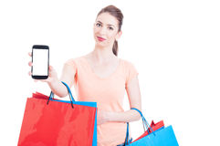 Woman carrying bunch of gift shopping bags showing blank cellphone Stock Photos