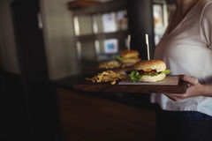Woman carrying burger and french fries in a tray at restaurant. Mid section of woman carrying burger and french fries in a tray at restaurant Stock Photography