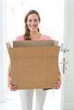 Woman carrying cardboard box in house Royalty Free Stock Images