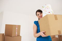 Woman Carrying Cardboard Box In New Home Royalty Free Stock Image