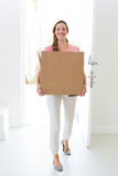 Woman carrying cardboard box in new house Stock Photo