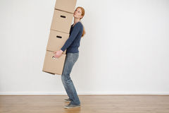 Woman Carrying Carton Storage Boxes. A young woman lifting a stack of carton moving boxes and carrying them in an empty room Royalty Free Stock Images