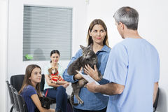Woman Carrying Cat While Looking At Nurse In Clinic Stock Photos