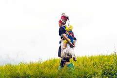 Woman carrying child. LAO CAI- VIETNAM: ethnic woman carrying her child on back in Bat Xat, Lao Cai province, Vietnam Royalty Free Stock Photo