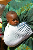 Woman carrying child in Mali. Woman carrying child during the market in Djenne - Mali Stock Images
