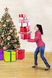 Woman carrying christmas gifts at home Royalty Free Stock Photography