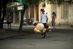 Woman carrying commodity on street in Hanoi,Vietnam. Royalty Free Stock Image