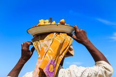 Woman carrying a dish with food on her head seen from behind Royalty Free Stock Images
