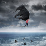 Woman carrying an elephant on the rope. Asian woman carrying an elephant while walking on the rope above the sea Royalty Free Stock Photo