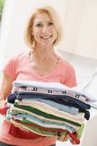 Woman Carrying Folded Up Laundry.  royalty free stock photos