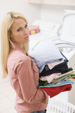 Woman Carrying Folded Up Laundry Royalty Free Stock Photography